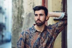 年轻有胡子的人,时尚模型,在都市后面的佩带的衬衣 库存图片