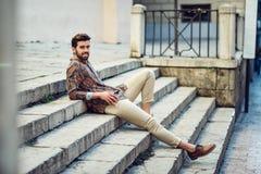 年轻有胡子的人,时尚模型,在都市后面的佩带的衬衣 免版税库存照片
