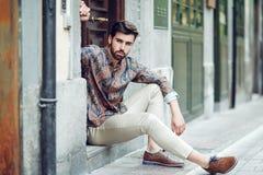 年轻有胡子的人,时尚模型,坐在都市步我们 免版税库存图片