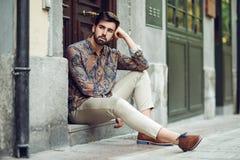 年轻有胡子的人,时尚模型,坐在都市步我们 免版税图库摄影