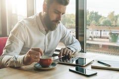 年轻有胡子的商人在办公室坐在桌上,使用片剂计算机,喝咖啡 在书桌上是笔记本,智能手机 免版税库存图片