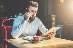 年轻有胡子的商人在咖啡馆在桌上,谈话坐手机,拿着片剂计算机 人工作 免版税库存照片