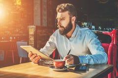 年轻有胡子的商人在咖啡馆在笔记本坐在桌上,拿着片剂计算机并且书写 库存照片