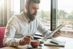 年轻有胡子的商人在咖啡馆坐在桌上,使用数字式片剂,喝咖啡 在书桌上是笔记本,智能手机 库存图片