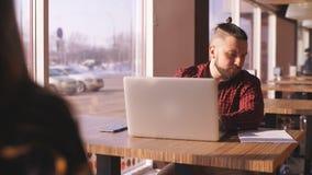 年轻有胡子的商人在咖啡馆坐在桌上 在桌膝上型计算机上 人是工作,学习 网上教育,营销 股票录像