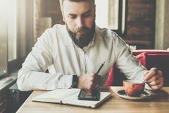 年轻有胡子的商人在咖啡馆,办公室在智能手机屏幕在他的手上坐在桌,举行笔上,读信息 库存照片