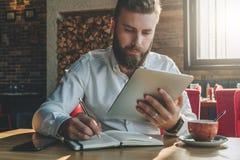 年轻有胡子的商人在咖啡馆,家在笔记本坐在桌上,看片剂计算机屏幕并且写 免版税图库摄影
