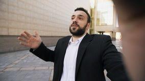 年轻有胡子的开商人谈的智能手机网上录影闲谈业务会议户外 库存图片