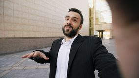 年轻有胡子的开商人谈的智能手机网上录影闲谈业务会议户外 免版税库存照片