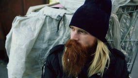 年轻有胡子的无家可归的人特写镜头坐在购物车upet附近和单独注重在街道 免版税库存照片