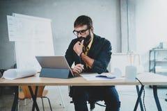 年轻有胡子的男性在一个数字式片剂船坞的建筑师佩带的眼睛玻璃工作他的书桌的 专家被体验 免版税库存图片