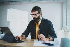 年轻有胡子的男性在一个数字式片剂船坞的建筑师佩带的眼睛玻璃工作他的书桌的 专家被体验 免版税库存照片