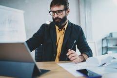 年轻有胡子的男性在数字式片剂船坞的建筑师佩带的眼睛玻璃工作播种的照片他的书桌的 免版税库存图片