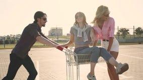 年轻朋友卷杂货推车 享用户外与购物台车种族的小组青年人在日落 股票录像