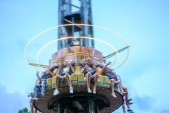 年轻朋友获得乐趣在公园 愉快的人在吸引力乘坐 娱乐公园,娱乐,天空兴奋 免版税库存照片