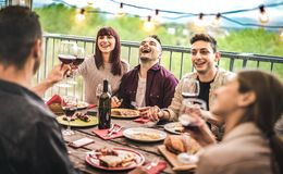 年轻朋友饮用乐趣饮用的红酒在阳台顶楼房屋晚餐会-吃bbq食物的愉快的人民在花梢选择 图库摄影