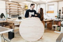 年轻木匠在木匠车间 人拿着文本的一个木圆的委员会 Copyspace 年轻专家,起动 库存图片