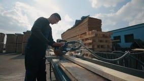 年轻木匠工作者佩带制服和使用木切割机 在背景的很多板台 宽看法 股票视频