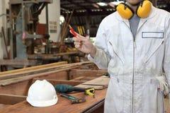 年轻木匠画象白色安全制服的在手上的拿着一支铅笔在木车间背景中 行业概念 库存照片