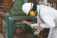 年轻木工作者侧视图白色安全制服的与刨床一起使用在工厂 库存照片