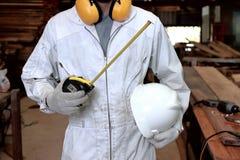 年轻木工作者和测量的磁带画象白色一致的举行的安全帽的在木匠业车间 免版税图库摄影