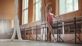 年轻杂技女孩显示身体的灵活性在芭蕾酒吧 免版税库存图片