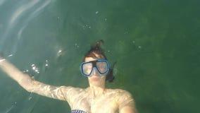 年轻棕色毛发的妇女Selfie说谎在水和在水面下与游泳面具,不用水肺晴天POV 股票视频