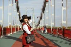 年轻模型时尚画象穿红色服装,黑帽会议, st 库存照片