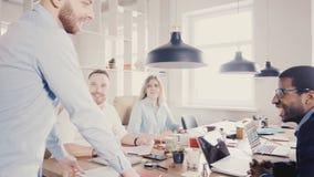 年轻欧洲上司激发并且鼓励同事 愉快的不同种族的工作者微笑,享用现代健康办公室4K 股票视频