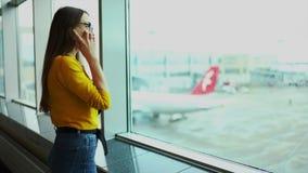 年轻欧洲妇女谈话在电话在错过飞行以后被弄翻和被挫败的机场终端窗口附近 影视素材
