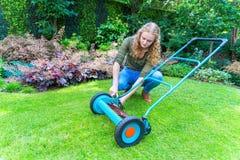 年轻欧洲妇女reparing的割草机在庭院里 库存照片