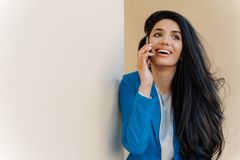 年轻正面女实业家在手机愉快地微笑,沟通,正式地穿戴,被聚焦某处,有最小的构成 免版税图库摄影