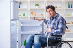 年轻残疾伤害了打开冰箱门的人 库存照片