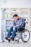 年轻残疾伤害了打开冰箱门的人 图库摄影