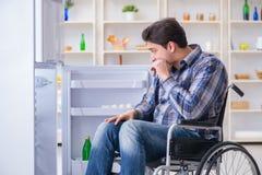 年轻残疾伤害了打开冰箱门的人 库存图片