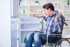 年轻残疾伤害了打开冰箱门的人 免版税库存图片