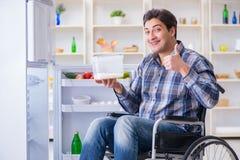 年轻残疾伤害了打开冰箱门的人 免版税库存照片