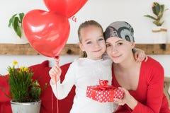 年轻母亲、癌症患者和她逗人喜爱的女儿,庆祝从医院的回归家 受欢迎的家或生日聚会 免版税图库摄影