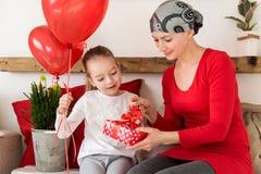 年轻母亲、癌症患者和她逗人喜爱的女儿,庆祝从医院的回归家 受欢迎的家或生日聚会 免版税库存图片