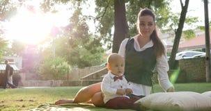 年轻母亲与衣服的逗人喜爱的婴孩和蝶形领结坐绿色草坪在公园 影视素材