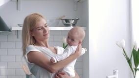年轻母亲举行画象手新生儿女孩的厨房,慈爱的父母轻轻地拥抱和亲吻的她的孩子 影视素材