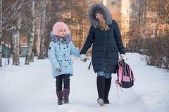 年轻母亲从学校带领女儿 免版税库存照片