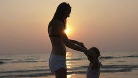 年轻母亲剪影有小的女儿跳舞的在日落的海滩 股票视频