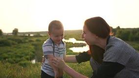 年轻母亲发痒她肚子的两岁的儿子在慢动作的自然 股票录像