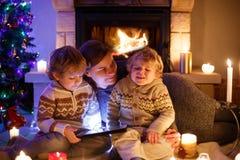年轻母亲和他的两个小孩在家由壁炉坐圣诞节时间 库存照片