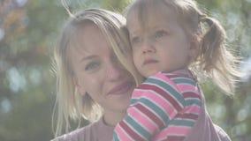年轻母亲和令人惊讶的白肤金发的女儿画象母亲手的 股票录像