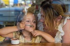年轻母亲和女儿吃在咖啡馆的冰淇淋,幸福家庭,看法通过窗口 免版税库存照片