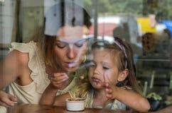 年轻母亲和女儿吃在咖啡馆的冰淇淋,幸福家庭,看法通过窗口 库存照片