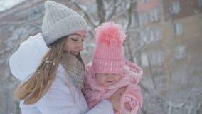 年轻母亲和女儿愉快一起在降雪在公园 股票录像
