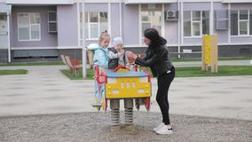 年轻母亲和她的两个孩子操场的,获得乐趣,生活方式 影视素材
